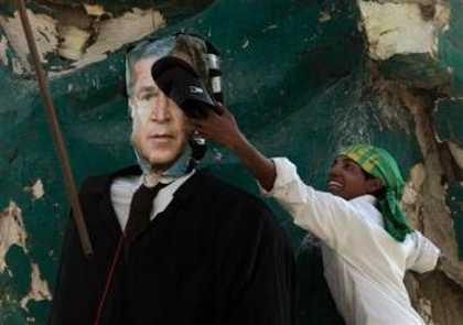Protester strikes Bush effigy